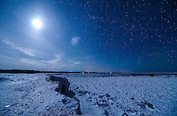 A view of the moon and a clear starry sky on a massive ice shelf on Lake Superior. Marquette, MI
