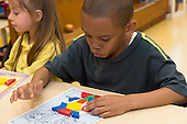 MR / Schenectady, NY. Zoller Elementary School (urban public school). Kindergarten inclusion classroom. Student (boy, 6, African American / Puerto Rican American) does manipulative activity with pattern card and pattern blocks during math learning center time. MR: Car38. ID: AM-gKw. © Ellen B. Senisi.