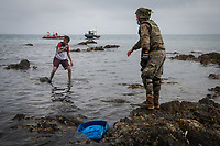 CEUTA, SPAIN ‐ MAY 19: A Spanish soldier talks to a migrant on the Tarajal beach to get him out of the water after having crossed the border between Morocco and Spain swimming on May 19, 2021 in Ceuta, Spain.  After a diplomatic conflict between Spain and Morocco, thousands of migrants who have taken advantage of the little Moroccan police activity on the border to cross it mainly by swimming, which has caused a migration crisis with the entry of more than 8000 migrants from the African country. (Photo by Joan Amengual/VIEWpress )