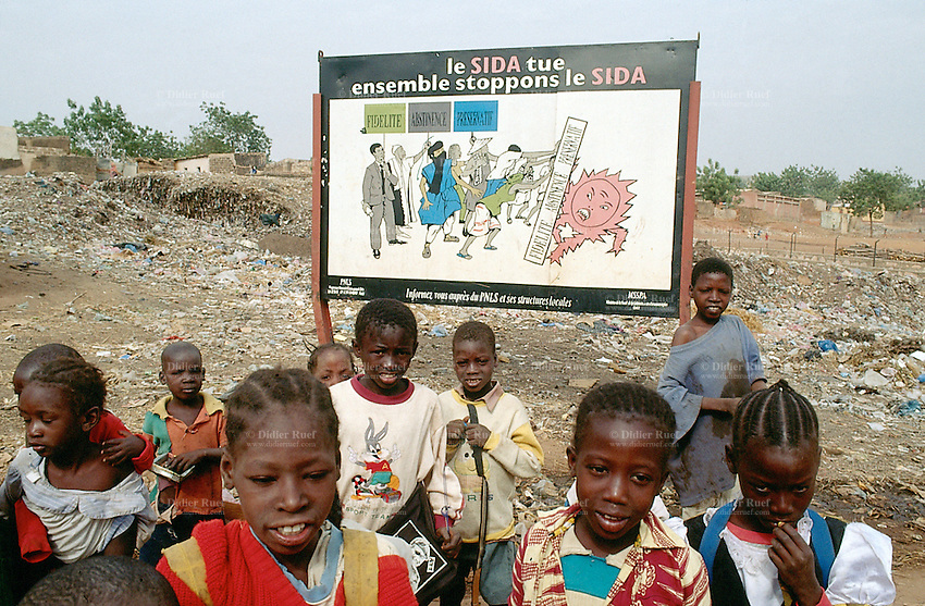 """Mali. Bamako. A group of children near a prevention poster on a Aids Hiv campaign, which says"""" Aids kills, stop Aids. Fidelity, abstinence, condom"""" . © 1997 Didier Ruef"""