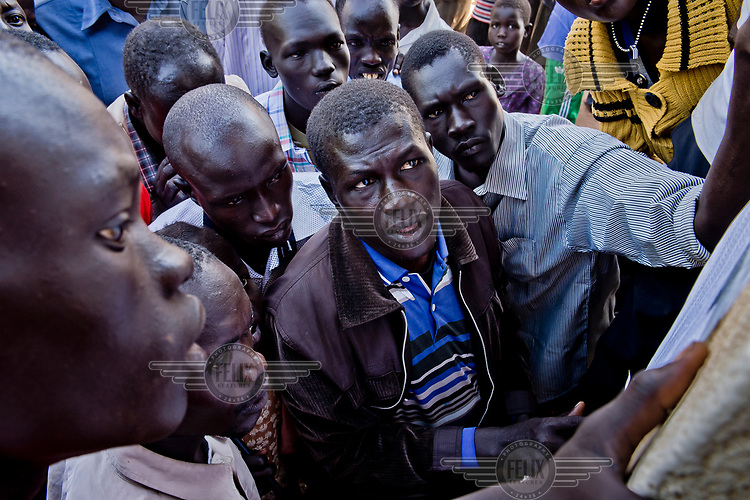 South Sudanese refugees look for their names on a list of those to be resettled on land at the Nyumanzi settlement, a few kilometre from the Dzaipi transit camp.