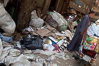 2011 Mokattam Garbage City (alla periferia del Cairo) il quartiere copto dove si vive in mezzo alla spazzatura raccolta: un motorino carico di immondizia, un uomo tra i rifiuti.The Coptic quarter where people live in the midst of garbage collection: a motor load of rubbish, a man ibetween trash.