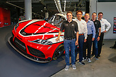 Toyota executives Ed Laukes and David Wilson, and Toyota Racing drivers Kyle Busch and Christopher Bell with Tetsuya Tada, chief engineer of the new Supra
