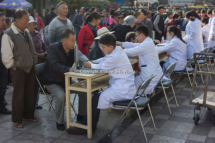 """Volunteer medical workers provide free checkup for residents in Gejiu, December 2014. Gejiu in Yunnan province is a """"Tin Centre"""" with more than 2,000 years of mining history. Tin articles made in Gejiu are highly acclaimed in China. However, the tin mining and related industries are in decline."""