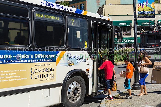 A Westchester County Bee-line System bus picks up passengers at a bus stop in Yonkers, New York.