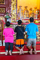 George Town, Penang, Malaysia.  Family Praying at Altar of Goddess of Mercy Temple, Kuan Yin Teng, Kong Hock Keong.