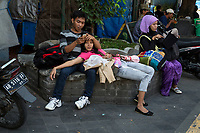 Yogyakarta, Java, Indonesia.  Young Couple on Malioboro Street, Early Morning.  Woman Using iPad.