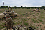 "American soldiers with Delta Company, 2nd Battalion, 7th Infantry Regiment, 1st Armored Brigade Combat Team, 3rd Infantry Division with M1A2 Abrams tanks after a tank training exercise practicing infiltration at the Drawsko Pomorskie Training Area in Poland on June 12, 2015.    NATO is engaged in a multilateral training exercise ""Saber Strike,"" the first time Poland has hosted such war games, involving the militaries of Canada, Denmark, Germany, Poland, and the United States."