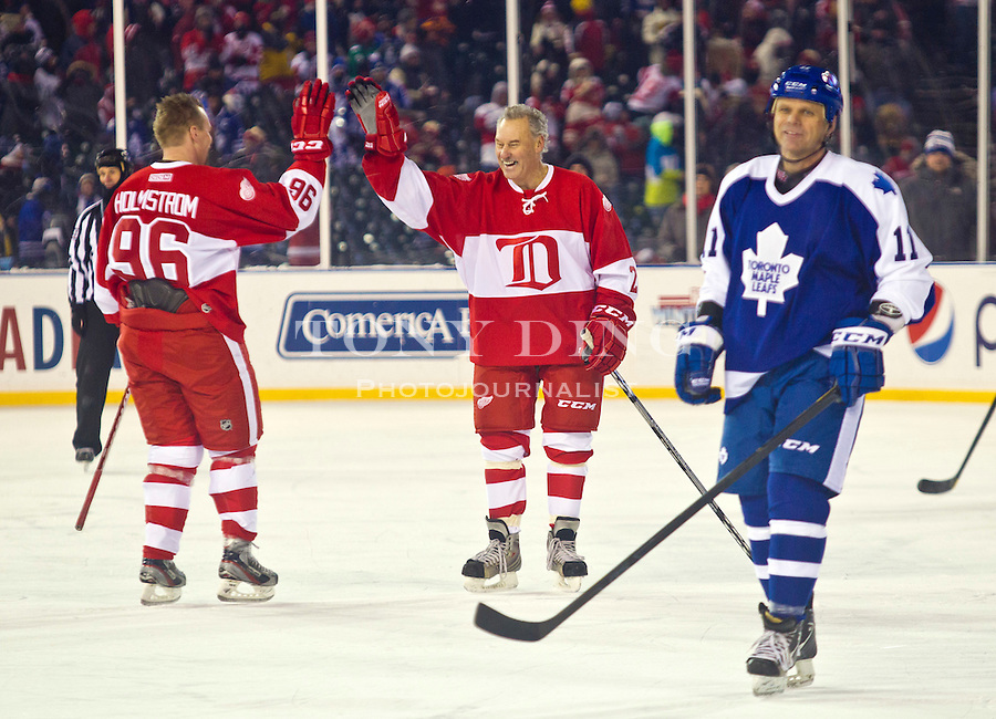 31 December 2013: Former Detroit Red Wings forward Tomas Holmstrom (96) celebrates his shootout goal with Red Wings legend Mickey Redmond, center, behind former Toronto Maple Leafs forward Steve Sullivan (11), during the Toronto Maple Leafs v Detroit Red Wings Alumni Showdown hockey game, at Comerica Park, in Detroit, MI. The Red Wings Alumni team won in shootouts.