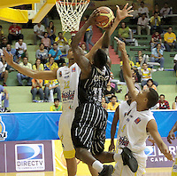 BUCARAMANGA -COLOMBIA, 30-05-2013. Thomas Tayron (C) de Piratas trata de anotar en contra Sergio Trocha (I) y Miguel Fernández (D) de Búcaros durante el juego 3 de los PlayOffs de la Liga DirecTV de baloncesto Profesional de Colombia realizado en el Coliseo Vicente Díaz Romero de Bucaramanga./ Thomas Tayron (R) of Piratas tries to score against Sergio Trocha (L) and Miguel Fernandez (R) of Bucaros during the PlayOffs game 3 of  DirecTV professional basketball League in Colombia at Vicente Diaz Romero coliseum in Bucaramanga. Photo:VizzorImage / Jaime Moreno / STR