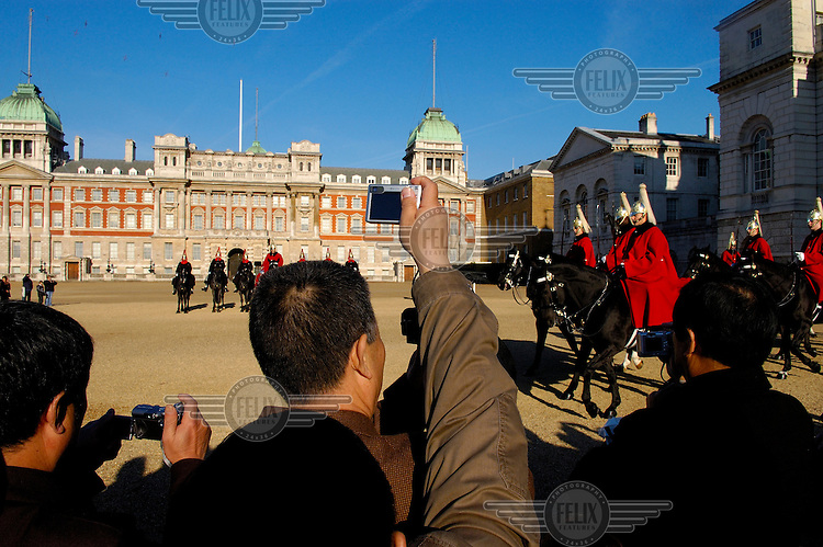 A group of Chinese tourists take photographs and watch the changing of the guard ceremony at Horse Guards Parade.