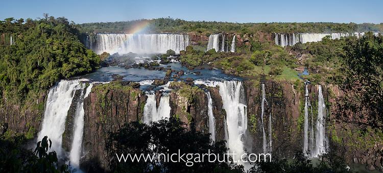 Morning rainbow at Iguasu Falls (also Iguazu Falls, Iguazú Falls, Iguassu Falls or Iguaçu Falls) on the Iguasu River, Brazil / Argentina border. Photographed from the Brazilian side of the Falls. State of Paraná, Brasil.