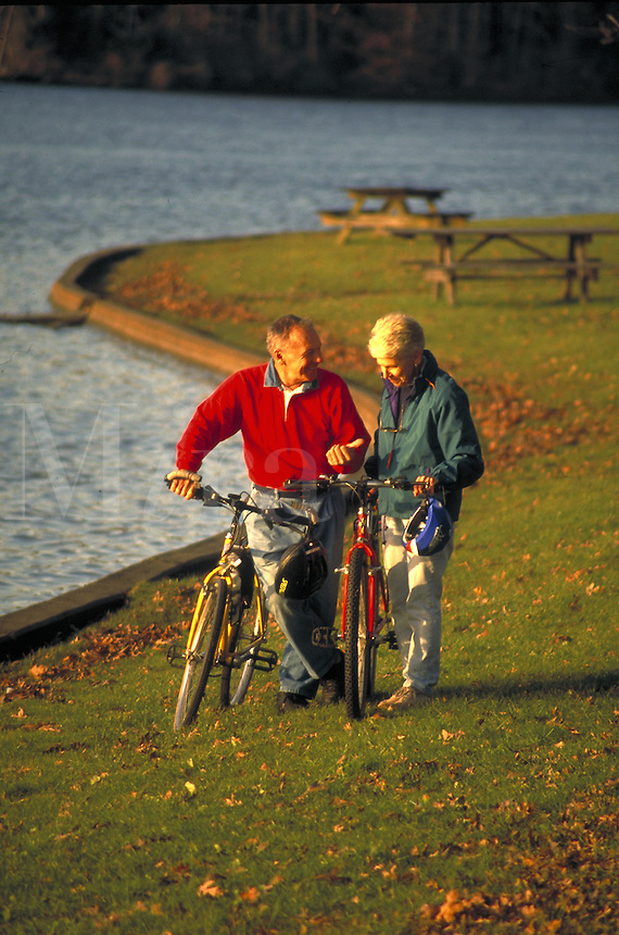 Senior couple biking at lake