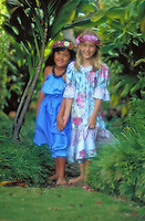 Two young girls, Hawaiian and Caucasian, walking through greenery