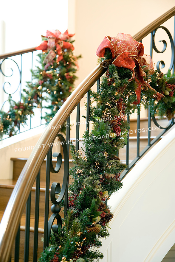 Evergreen garland, accented with vibrant red bows, winds its way up both sides of the stairs to create a festive holiday display.
