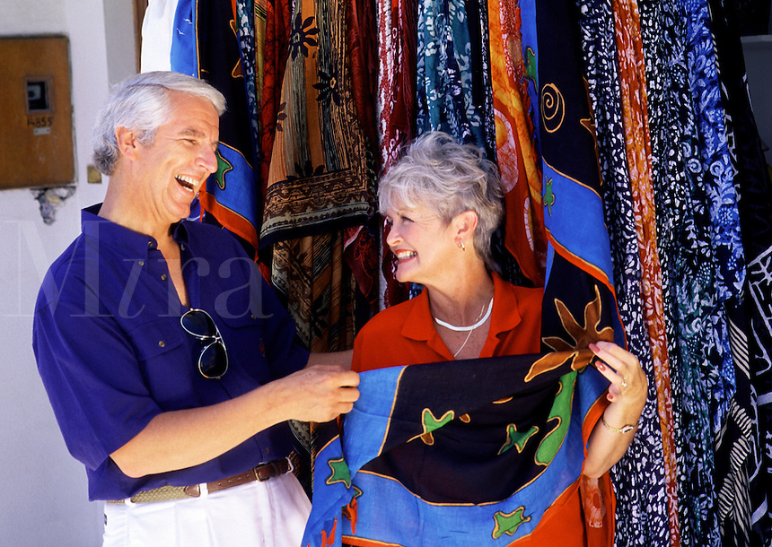 A laughing senior couple shopping for brightly colored cloth. Greece.