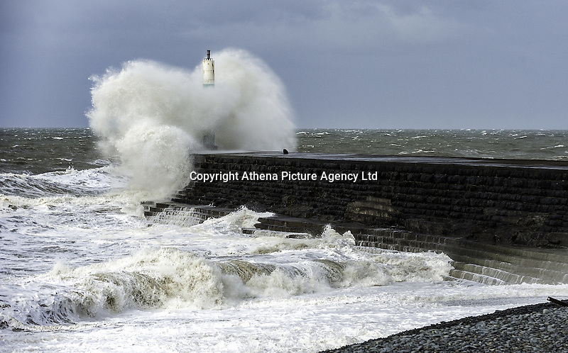 """WEATHER PICTURE WALES<br /> Pictured: Waves crash against the lighthouse and harbour wall in Aberystwyth, Ceredigion, Wales. Wednesday 02 March 2016<br /> Re: Roads have been closed, homes left without power and tiles blown from roofs after Storm Jake brought wintry showers and high winds to Wales.<br /> Yellow Met Office """"be aware"""" warnings of snow, ice and wind were issued for most of Wales for Wednesday morning.<br /> Gusts - forecast to reach up to 70mph - caused roof tiles to fall and trees to be blown over in Aberystwyth, with roads closed as a precaution."""