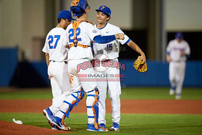Florida Gators relief pitcher Jordan Butler (15), catcher JJ Schwarz (22) and designated hitter Nelson Maldonado (27) celebrate after closing out a game against the Siena Saints on February 16, 2018 at Alfred A. McKethan Stadium in Gainesville, Florida.  Florida defeated Siena 7-1.  (Mike Janes/Four Seam Images)