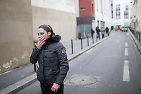 An undercover police woman covers her mouth near the site of the massacre at Charlie Hebdo in Paris where masked gunmen killed 12 people. Paris, France, (Jan. 7, 2015).