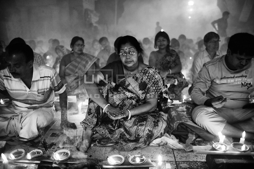 """During Kartik, """"the holiest month"""" beginning every year with the new moon in November, thousands of Hindu devotees celebrate the feast of Rakher Upobash, fasting and praying the gods sitting before the Shri Shri Lokanath Brahmachari Ashram, among the Swami Bagh Temple near Dhaka, Bangladesh. The worshippers offer candles called Prodip, meditate, give to charity, and generally perform austerity. A Woman prays during the celebration.<br />  Barodi, Dhaka, Bangladesh. Nov. 15, 2014"""