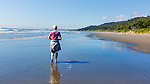 Senior Woman walking on Kalaloch Beach State Park, Washington.  Beaches in the Kalaloch area of Olympic National Park, identified by trail numbers, are remote and wild.  Olympic Peninsula, Olympic Mountains, Olympic National Park, Washington State, USA.