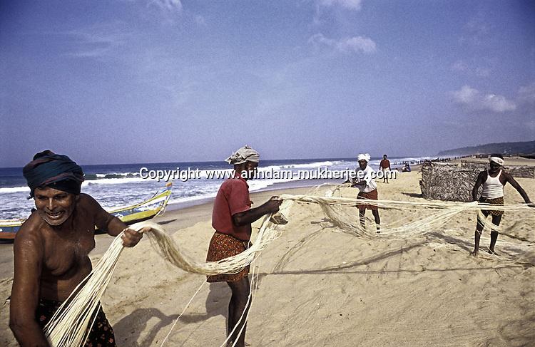 Fishermen working at Chowra beach near Kovalam, Trivendrum, Kerala, India.