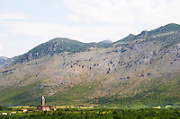 A church on the plain dominated by the Kastrat Shkrel mountains near Koplik and the Montenegro border. Albania, Balkan, Europe.