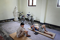 CHINA. Hangzhou. Workers take a rest inside a church that is being renovated. During the Cultural Revolution, the church was used as a prison. 2009