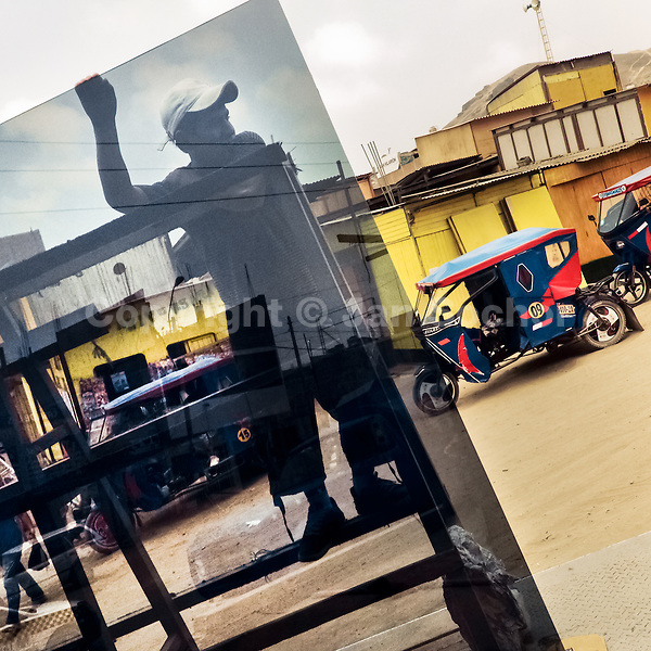 A Peruvian worker unloads a large window glass from a truck on the street of Pachacútec, a desert shantytown in Lima, Peru, 20 January 2015.
