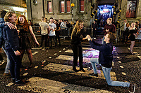 Pictured: Chris Williams (R) proposes to his girlfriend Beth Marchant to the amusement of friends and passers-by on the zebra crossing in Wind Street, Swansea. Sunday 31 December 2017 and 01 January 2018<br /> Re: New Year revellers in Wind Street, Swansea, Wales, UK