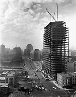 Vue panoramique du siège social d'Hydro-Québec en construction.<br /> À côté, on aperçoit l'emplacement du futur Complexe Desjardins, occupé par un stationnement, et au loin la Place Ville-Marie.<br /> 1962.<br /> Source : Archives d'Hydro-Québec, H2/663_4.