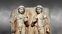 Close up of a Roman Sebasteion relief  sculpture of  Two princes, Aphrodisias Museum, Aphrodisias, Turkey. Against a grey background.<br /> <br /> Two princes stand like statues, naked, wearing cloaks. The left figure holds the orb of the world in one hand, a symbol of  world rule that indicates he is the imperial heir, and in the other a ship's stern ornament (aphlaston), a symbol of naval victory. They and probably Gius and Lucius, the grandsons of Augustus, or Nero and Britanicus, Claudius' heir.