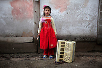 A girl poses with an accordion. Buzescu is known for it's ultra-wealthy Roma and their bizarre mansions that line the main street. The Roma of Buzescu are part of the Kalderash clan and are known for being coppersmiths and dealing with metal scraps. After the fall of the communist regime in the late 80's, they stripped old factories of their metals and some made a small fortune re-selling them. They are also known for making cazane, copper stills that produce alcohol such as palinka, a plum brandy.