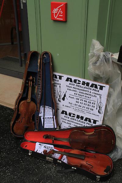 Violins for sale on Rue Cler in Paris, France.