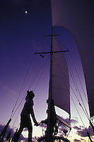 Man trimming sails after sunset aboard sailing yacht 'Heron', a Halberg-Rassy 46, in tropical waters with moon in background