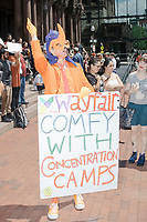 """A man dressed in an orange costume holds a sign reading """"Wayfair: comfy with concentration camps,"""" as Wayfair employees demonstrate in Copley Square to protest their company's sale of furniture to detainment camps for children operated by US Customs & Border Protection (CBP) on the Mexico border in Boston, Massachusetts, USA, on Wed., June 26, 2019. Wayfair is an online furniture retailer. Employees are asking for the company to set ethics standards for sales. The Wayfair employees were joined by union representatives, PRIDE activists, and other groups in solidarity.  This action occurred the week after US government legal representatives argued that children held in CBP facilities did not need soap or beds to meet the """"safe and sanitary"""" standard of care required by law after months and years of criticism of Trump administration policies of family separation and cruel treatment of those held at its facilities."""