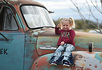 Lydia Montgomery, 5, sits on a truck as she poses for pictures, Thursday, October 15, 2020 at the Benton County Fairgrounds in Bentonville. The 4th annual Fall Y'all Craft Fair featured 40 vendors, half capacity to previous years, as well as local food trucks, photo opportunities and a pumpkin patch. The fair ends on Sunday. Check out nwaonline.com/2010013Daily/ for today's photo gallery. <br /> (NWA Democrat-Gazette/Charlie Kaijo)