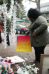 NEWTOWN, CT-17 December 2012-121712LW03 - Eboni Johnson of Hartford places a supportive sign at the site of a makeshift memorial in Newtown at the corner of Washington Avenue and Church Hill Road Monday. Laraine Weschler
