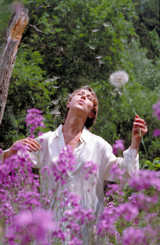 Young woman in a field of purple Spring Flowers blowing the spores off a puffball. flowering plants, leisure, relaxation. N. Dowd, M.R. #n-4. Colorado, outdoors.