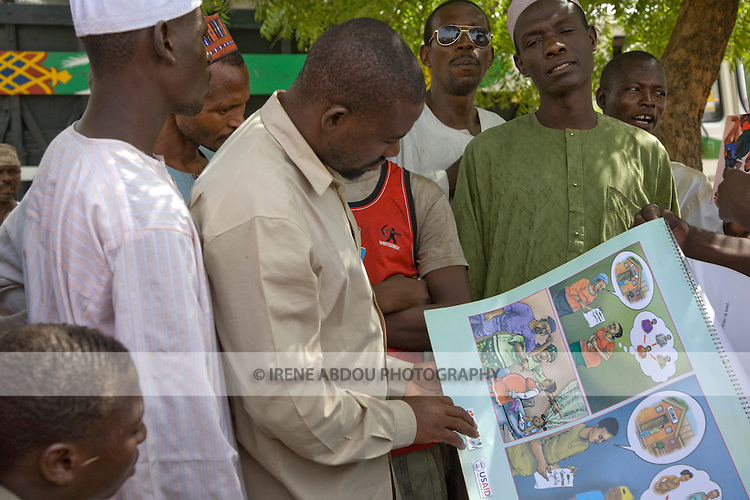 A man in Yankaba market (Nassarawa area, Kano, Nigeria) looks at a flipchart depicting how partner reduction reduces chances of HIV/AIDS transmission, The flipchart was developed by the Society for Family Health (SFH), with funding from the US Agency for International Development (USAID).  SFH is Nigeria's largest indigenous NGO and partner of the international social marketing organization, Population Services International (PSI).