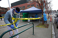 Health care workers from the International Community Health Services (ICHS) set up a drive-through testing site for COVID-19 outside their International District location on March 26, 2020 in Seattle, Washington. Non-profit community health centers across the country are suffering financially at a time when the community most needs them. Serving uninsured, low income, and immigrant communities, many who rely on federal aid programs, the COVID-19 pandemic has devastated their finances at a time when they are gravely needed. The lack of federal response to aid community clinics has led to furloughs, alterations of operations and a decrease in patients that may result in long-lasting, devastating impacts. (photo by Karen Ducey)