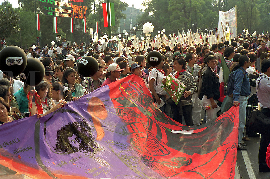 March on Avenida Reforma to the Zocalo in support of EZLN (Ejercito Zapatista de Liberacion Nacional), the Zapatista agrarian reform movement. Balloons depicting hooded revolutionary, image of Zapata on banner. Mexico City Mexico D.F. Mexico.