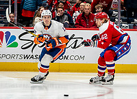 WASHINGTON, DC - JANUARY 31: Mathew Barzal #13 of the New York Islanders sends a pass away from Carl Hagelin #62 of the Washington Capitals during a game between New York Islanders and Washington Capitals at Capital One Arena on January 31, 2020 in Washington, DC.