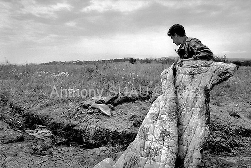 Morina, Kosovo  <br /> 1999<br /> <br /> Two rotting corpses are covered by a KLA member. They were just two of the thousands of executed Albanians that the Serbs killed and dumped throughout the country.