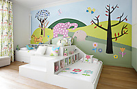 A modular two bed unit with built-in storage in a children's bedroom. A colourful, fun mural is painted on one wall.