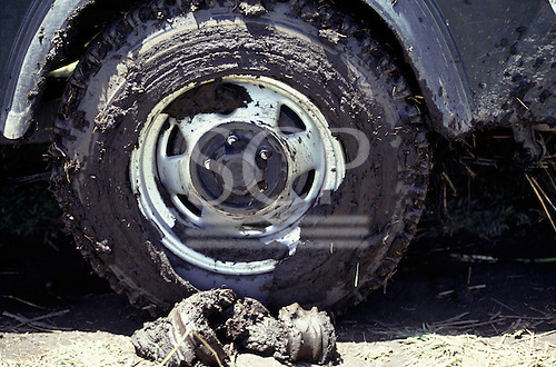 Chipundu, Zambia. Mud-coated wheel of a four wheel drive Jeep.