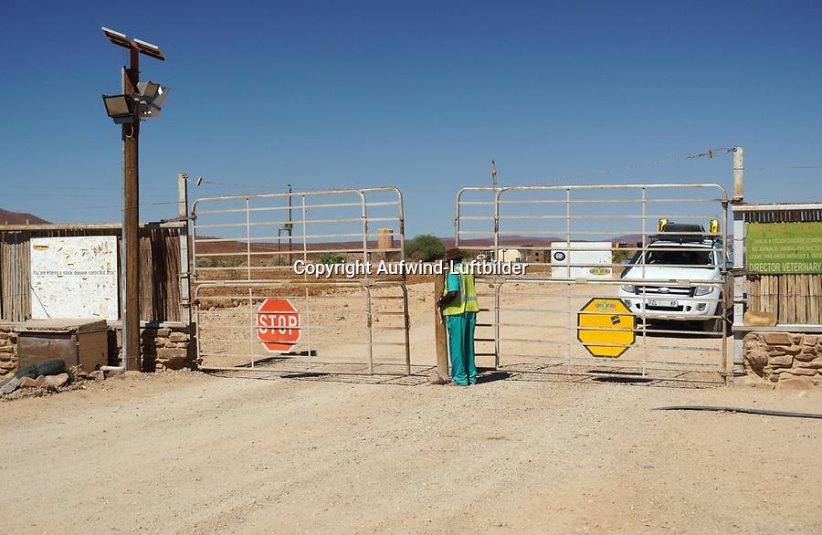 """Grenzverlauf zwischen Nambia und Botwana: NAMIBIA, AFRIKA, 12.12.2019: Rote Linie.<br /> Der Zaun verläuft von der Küste im Westen nach Osten bis an die Grenze zu Botswana und entlang dieser. Er wurde kurz nach einem Ausbruch der Rinderpest im Jahr 1897 angedacht, Mitte der 1960er Jahre endgültig errichtet und besteht – in weiten Teilen – bis heute.<br /> Er soll eine unkontrollierte Bewegung von Fleisch, Vieh und tierischen Produkten von Norden nach Süden unterbinden. 1961, als es zu einem starken Ausbruch der Maul- und Klauenseuche im Norden Namibias kam, wurde der Zaun erneut verstärkt. Bis zum Ende der Apartheid mit der Unabhängigkeit Namibias im Jahr 1990, aber auch schon in der deutschen Kolonialzeit, hatte der Zaun jedoch eine weitere Funktion: Die im Norden Namibias lebenden Stämme konnten dadurch leichter vom ansonsten """"weißen"""" Namibia, der Polizeizone, ferngehalten werden. So kam diese """"rote Linie"""" den Südafrikanern bei der Durchsetzung ihrer Homeland-Politik sehr gelegen und bis 1977 durfte kein Ovambo diese Grenze ohne Genehmigung (z. B. in Form eines Arbeitsvertrages) überqueren."""