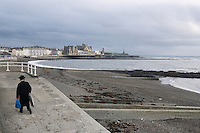 An Hasidic man walks away after spending the afternoon on the beach in Aberystwyth.