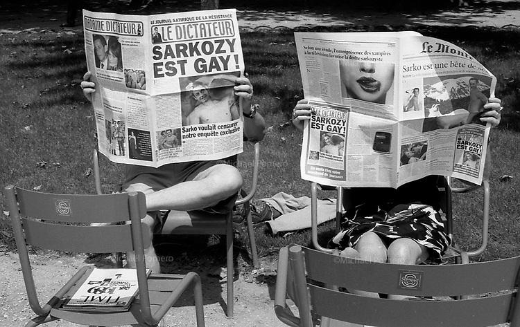 07.2009 <br /> <br /> Couple reading satirics newspapers (saying that president Sarkozy is gay) in luxembourg garden.<br /> <br /> Couple lisant des journeaux saririques (disant que Sarkozy est gay) dans le jardin du luxembourg.