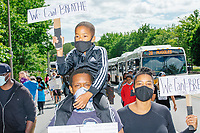 """People take part in the """"Peaceful Children's March: Be the Change"""" demonstration in support of Black Lives Matter in Nubian Square in Boston, Massachusetts, on Sun., June 7, 2020. The children's march was organized by siblings Naheem, 7, and Anaysha Benalfew, 10. The demonstration is part of a weeks-long nationwide response to the killing of George Floyd by Minneapolis police on May 25, 2020. The march started near the Nubian Square bus depot and continued to the nearby Boston Police Department headquarters, where marchers knelt for 8 minutes and 46 seconds, the time that police officers knelt on George Floyd's neck during his killing. A number of children, mostly people of color, then spoke about how people should be treated equally and how they wished they didn't have to grow up fearful that a police officer would kill them or their loved ones.  The signs here read """"We Can't Breathe."""""""